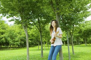 公園の木陰でウクレレを弾く20代女性の写真素材 [FYI03924028]