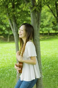 公園の木陰でウクレレを弾く20代女性の写真素材 [FYI03924029]