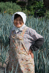 畑と農家の中高年女性の笑顔の写真素材 [FYI03924257]