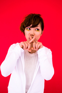 口元を指で交差する女性の写真素材 [FYI03924277]