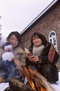 雪の中で火を囲む女性の写真素材 [FYI03925232]