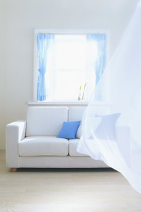青いカーテンの窓辺とソファーの写真素材 [FYI03925661]