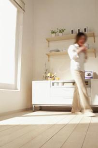 室内を歩く女性 ブレの写真素材 [FYI03925689]