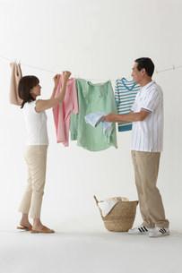 洗濯物を干すカップルの写真素材 [FYI03926443]