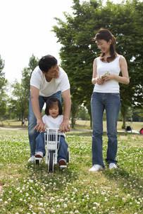 三輪車に乗る娘と両親の写真素材 [FYI03926469]