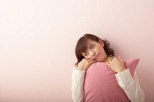 クッションを抱える女性の写真素材 [FYI03926922]