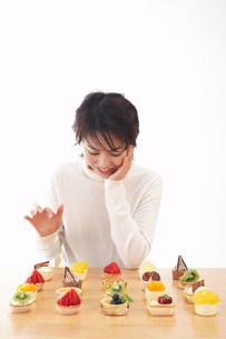 たくさんのケーキと女性の写真素材 [FYI03926962]