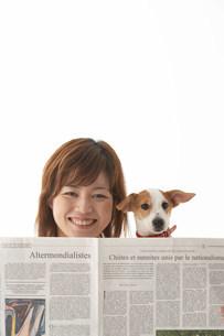 新聞を読む女性と犬の写真素材 [FYI03927087]