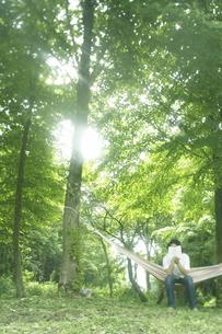 新緑林で読書する男性の写真素材 [FYI03927307]