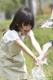 公園のポンプから水をすくう女の子の写真素材 [FYI03927714]