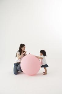 風船で遊ぶ女の子と母親の写真素材 [FYI03927990]