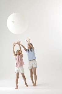 風船で遊ぶ姉妹の写真素材 [FYI03928000]