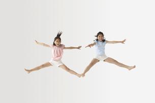 ジャンプする姉妹の写真素材 [FYI03928001]