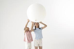 風船で遊ぶ姉妹の写真素材 [FYI03928004]