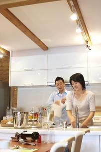 キッチンで洗い物をする夫婦の写真素材 [FYI03928020]