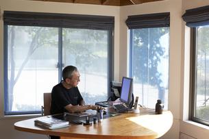 書斎でパソコンを見る男性の写真素材 [FYI03928021]
