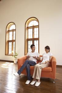 リビングのソファーで話をする夫婦の写真素材 [FYI03928030]
