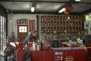 休日にガレージでバイクを整備する男性の写真素材 [FYI03928069]
