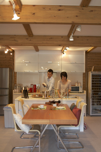 キッチンで食後のかたづけをする夫婦の写真素材 [FYI03928078]