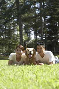 芝生の上の夫婦と犬の写真素材 [FYI03928108]