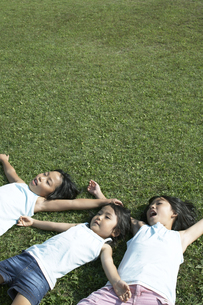 芝生で昼寝をする三姉妹の写真素材 [FYI03928130]