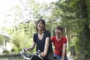 森を自転車で走る女性二人の写真素材 [FYI03928148]