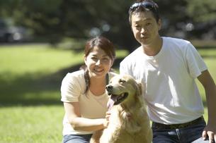 芝生と夫婦と犬の写真素材 [FYI03928156]