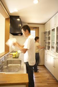 キッチンで食後のかたづけをする夫婦の写真素材 [FYI03928179]