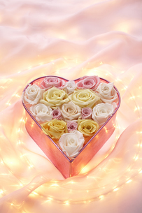 ハート型のケースとバラの造花と光の写真素材 [FYI03928272]