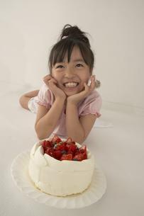 寝ころんで笑顔の女の子とケーキの写真素材 [FYI03928460]