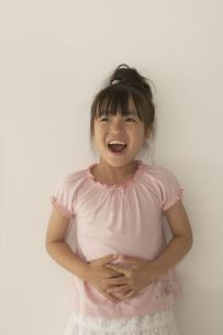 壁際に立つ笑顔の女の子の写真素材 [FYI03928461]