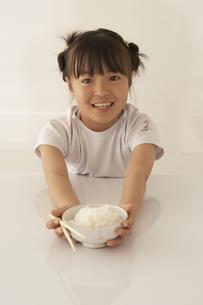 茶碗と箸を持っている女の子の写真素材 [FYI03928464]