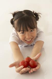 ミニトマトを差し出す女の子の写真素材 [FYI03928469]