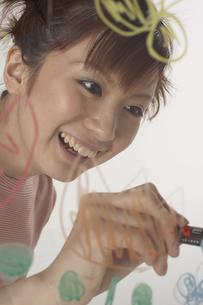 ガラスに絵を描く女性の写真素材 [FYI03928503]