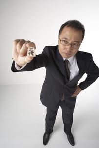 将棋の駒を持つスーツを着た男性の写真素材 [FYI03928504]
