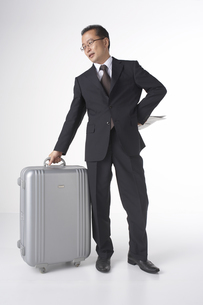 スーツケースを持っているスーツを着た男性の写真素材 [FYI03928505]
