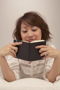 ソファーでスケジュール帳を見ている女性の写真素材 [FYI03928524]