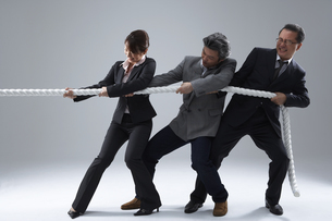 綱引きをするスーツを着た男女の写真素材 [FYI03928527]