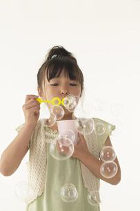 シャボン玉で遊んでいる女の子の写真素材 [FYI03928568]