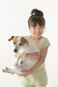 犬を抱いている女の子の写真素材 [FYI03928570]