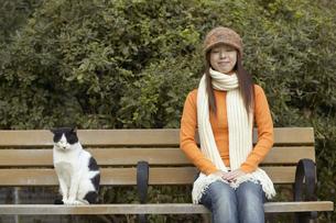 公園のベンチに座っている女性と猫の写真素材 [FYI03928578]