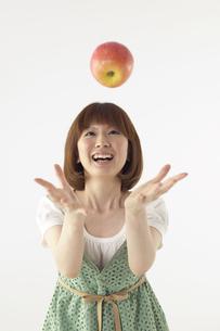 リンゴを投げている女性の写真素材 [FYI03928598]
