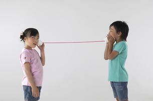 糸電話で遊んでいる男の子と女の子の写真素材 [FYI03928621]