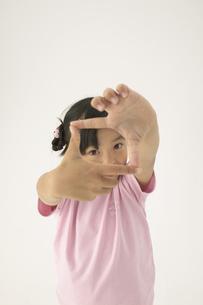 手で四角を作っている女の子の写真素材 [FYI03928629]