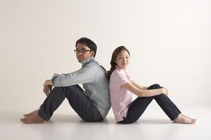 背中合わせで座っている男性と女性の写真素材 [FYI03928658]
