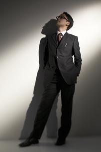 スーツを着て壁際に立つ男性の写真素材 [FYI03928666]