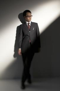 スーツを着て壁際に立つ男性の写真素材 [FYI03928672]