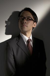 スーツを着て壁際に立つ男性の写真素材 [FYI03928673]