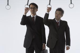吊革につかまっている二人のビジネスマンの写真素材 [FYI03928677]