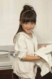 お皿を拭いている女の子の写真素材 [FYI03928708]
